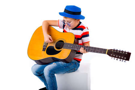 A boy kid plays guitar on a white background in the studio. Standard-Bild