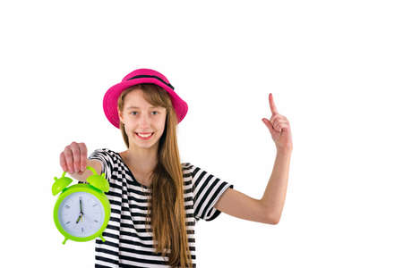 Teen Girl holding alarm Clock,poke at copy space.Portrait of caucasian teenager showing green alarm clock.Copy space.