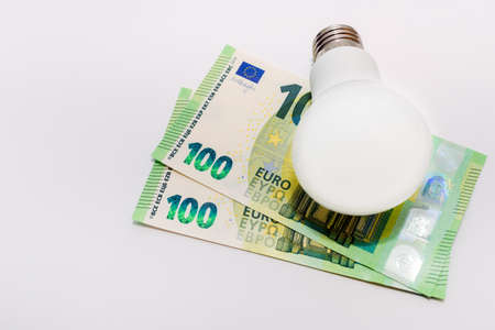 One LED bulb and 100 euro bills on white light background