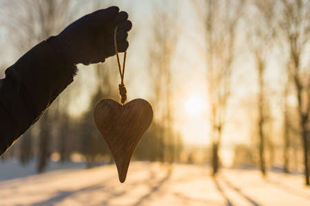 Womans hand holding a wooden heart on winter snowy forest evening blurred background. Love winter or St. Valentine's day concept. Selective focus.