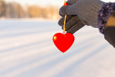 Hand holding red heart up to the sun during sunset.Winter snowy background.
