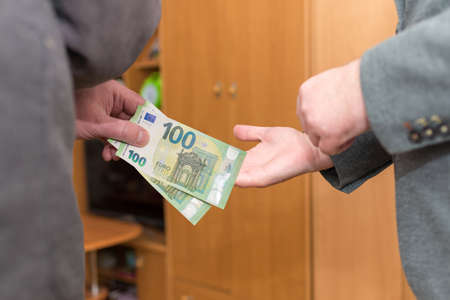 Hand giving money like bribe or tips or salary hard worked hand taking 100 euro banknotes.