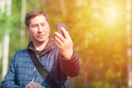 One 40s man with his mobile smart phone searching for reception signal in the spring sunny forest.