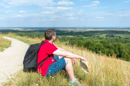 Traveler male relaxing meditation with serene view mountains forest landscape summer day. Man enjoying a view from the top of mountain. Relaxing middle age man alone with nature.