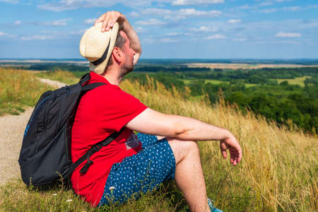 Traveler male relaxing meditation with serene view mountains forest landscape summer day. Man enjoying a view from the top of mountain. Relaxing middle age man alone with nature.Closeup,side view.