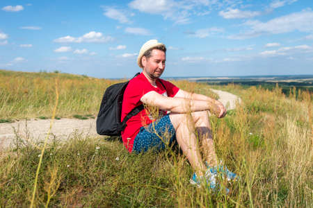 Traveler male relaxing meditation with serene view mountains forest landscape summer day. Man enjoying a view from the top of mountain. Relaxing middle age man alone with nature. Zdjęcie Seryjne