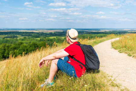 Traveler male relaxing meditation with serene view mountains forest landscape summer day. Man enjoying a view from the top of mountain. Relaxing middle age man alone with nature.Closeup,side view. Zdjęcie Seryjne