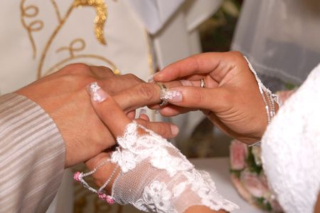 Groom Putting Ring on Brides Finger photo