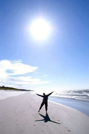 Woman exercises yoga on beach in radii of  sun  photo