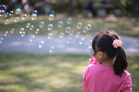 blowing: Little girl blowing bubbles under the sun