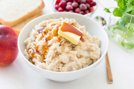 breakfast food: Bowl of oatmeal porridge with butter and maple syrup. Breakfast food still life