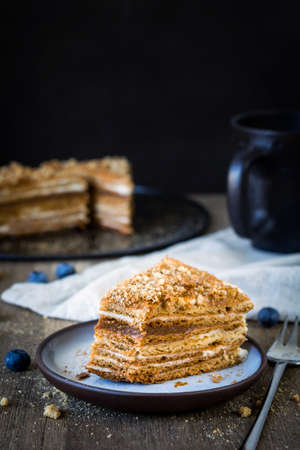 honey tone: Slice of homemade medovik layered honey cake, traditional russian cake with cream and caramel on plate on rustic wooden table. Vertical composition, selective focus, cold tone
