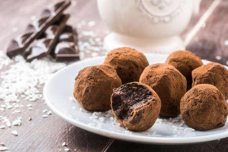 날짜, 코코넛 플레이크, 압연 귀리와 함께 만든 건강한 채식 초콜릿 트뤼플 흰색 접시에 제공