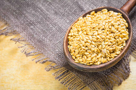 lipoprotein: Golden linseeds flax seeds in wooden spoon on linen cloth, close up