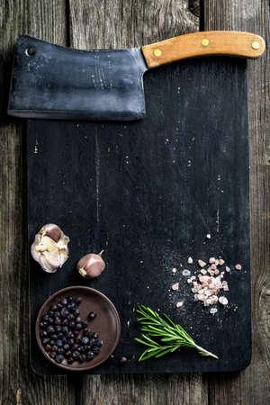 sal: Antiguo cuchillo de la cuchilla de carnicero carne y especias sobre tabla de cortar de madera, textura de fondo. Cocinar los ingredientes. Espacio de la copia. Maqueta de libro de cocina Foto de archivo