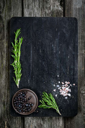 Rosemary, salt and pepper on wooden cutting board, copy space. Cooking food background