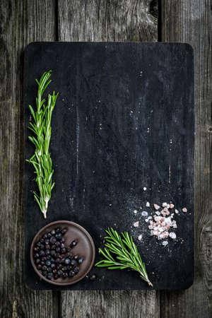 Rozemarijn, zout en peper op houten snijplank, kopie ruimte. Koken voedsel achtergrond Stockfoto