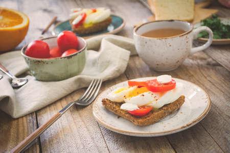 niños desayunando: Mesa de desayuno saludable: tostadas, huevos, frutas, verduras y té verde