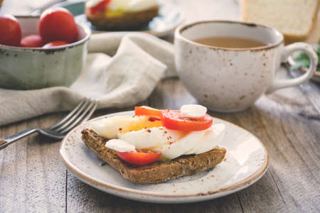 Healthy Breakfast table: toasts, eggs, fruits, vegetables and green tea Stock Photo