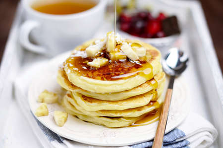 Pancakes with banana and coconut on white plate, cup of green tea, tea spoon and cranberries on white tray, close up Stock Photo