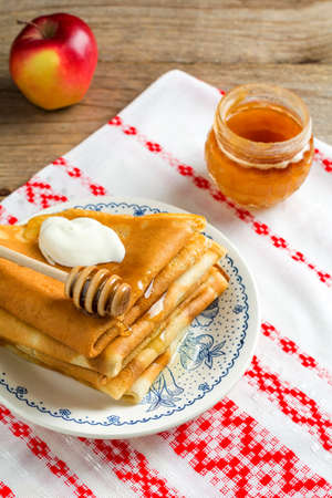 blini: Stack of crepes russian blini with sour cream and honey for Maslenitsa Stock Photo