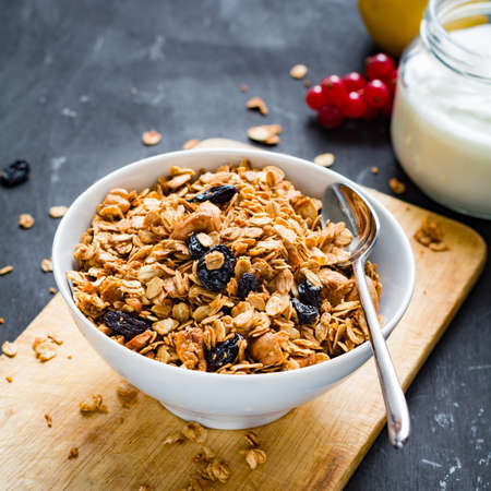 Homemade granola with nuts and dried fruits in white bowl, jar of fresh yogurt and fruits on wooden background