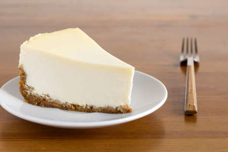 Slice of Plain New York Cheesecake on white plate on wooden background Foto de archivo