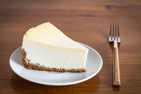 Slice of Plain New York Cheesecake on white plate on wooden background Stock Photo