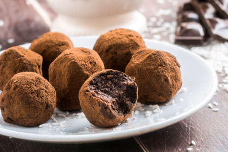 sweet foods: Homemade healthy vegan chocolate truffles with dates, coconut flakes and rolled oats served on white plate