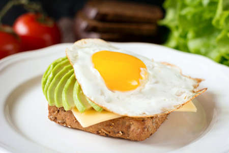 sunny side up: Sunny side up egg, avocado and cheese on whole grain toast for healthy breakfast