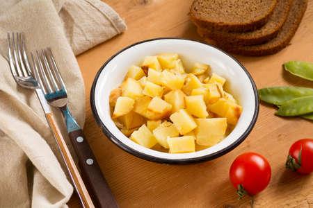 ensalada tomate: ensalada de papa sana en un tazón en el fondo de madera rústica