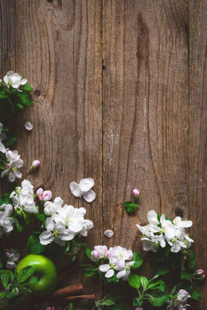 post card: Apple blossoms and green apples on rustic wooden background. Copy space for text. Post card, gift card or wedding card template. Design background