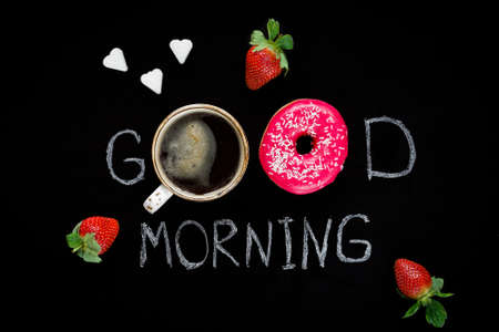 Donuts and strawberries. Good morning greeting written on black chalk board. Table top view. Breakfast food concept.