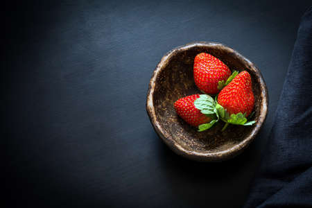 Fresh strawberries in a bowl on black background, top view. Still life