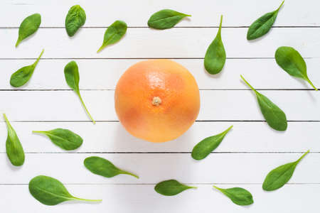 Fruit pattern. Spinach leaves and red grapefruit on white wooden planks background. Flat lay of fresh healthy food ingredients. Healthy green vegan lifestyle concept Stock Photo