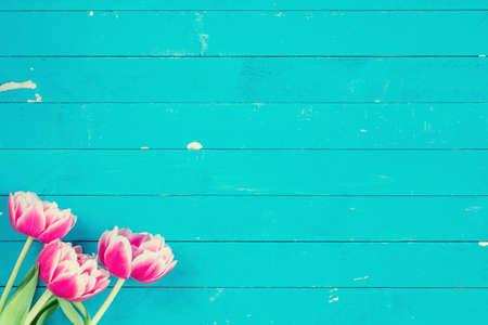azul turqueza: Tarjeta floral. Tres flores de color rosa sobre fondo azul turquesa de la vendimia, copia espacio para el texto, horizontal Foto de archivo