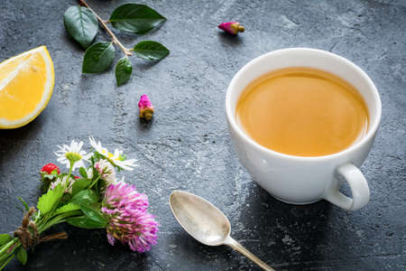 lemon wedge: Cup of green tea, lemon wedge, rose buds and bouquet of flowers. Concept of antioxidant beverage, healthy lifestyle, dieting, well-being. Horizontal Stock Photo