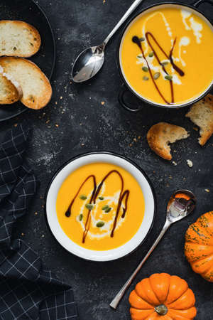 comfort food: Pumpkin cream soup in bowl garnished with heavy cream, pumpkin seeds and balsamic vinegar. Top view. Comfort food, fall  autumn concept.