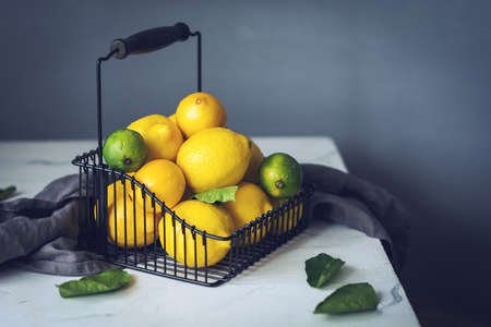 Citrus fruits in bakset on marble table Stock Photo