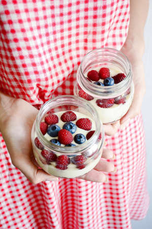 Yogurt with fresh raspberry and blueberry in jar in woman hands. Vertical