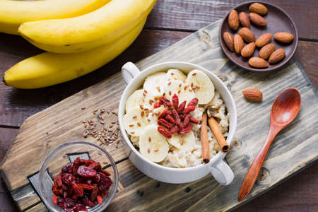 Oatmeal porridge with banana, cinnamon, dry goji berries and flax seeds on wooden cutting board. Healthy food, healthy lifestyle, diet, vegan, wellbeing concept. Horizontal, overhead view