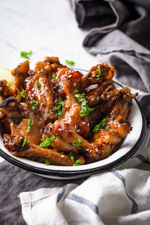 lemon wedge: Teriyaki chicken wings in white bowl garnished with sesame seeds, chopped parsley and lemon wedge on marble table. Side view, toned, vertical