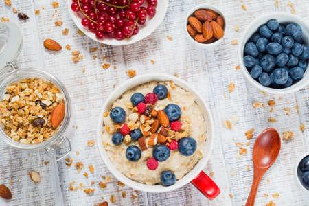 oatmeal: Healthy breakfast: oatmeal porridge with fresh blueberries, raspberries and muesli. Overhead view Stock Photo