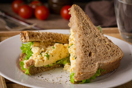 whole wheat toast: Breakfast sandwich with scrambled eggs, fresh green salad and whole wheat bread. Close up view, horizontal Stock Photo