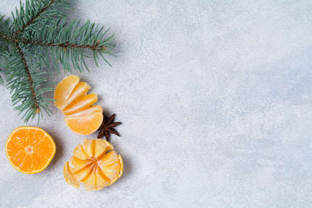 Winter composition with tangerines, spices, almonds and fir tree on blue background. Top view, copy space for text