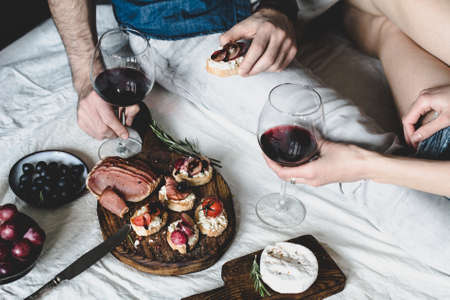 Couple having dinner with red wine and antipasto snacks set: bruschettas, crostini, prosciutto, camambert cheese, grapes and black olives. Selective focus, desaturated effect.