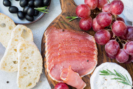 Cured meat, fresh baguette, grapes, cheese and black olives. Italian antipasti set. Close up view Stock Photo