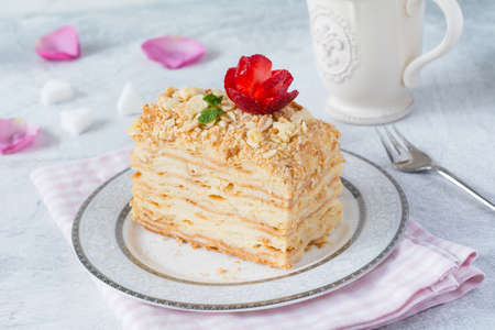 Napoleon cake, layered cake with pastry cream, custard decorated with strawberry rose and mint. Close up view. Piece of homemade cake