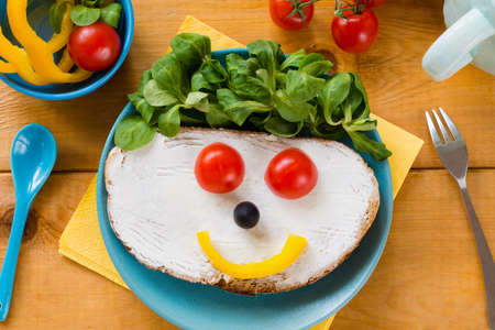 breakfast smiley face: Kids meal, breakfast or lunch for children. Colorful funny food face with healthy vegetables, cheese spread and green salad on a plate. Concept of healthy food, healthy breakfast. Top view, closeup