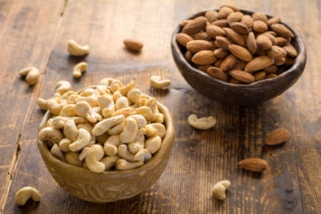 Cashews and almonds in bowl on textured wooden background. Selective focus